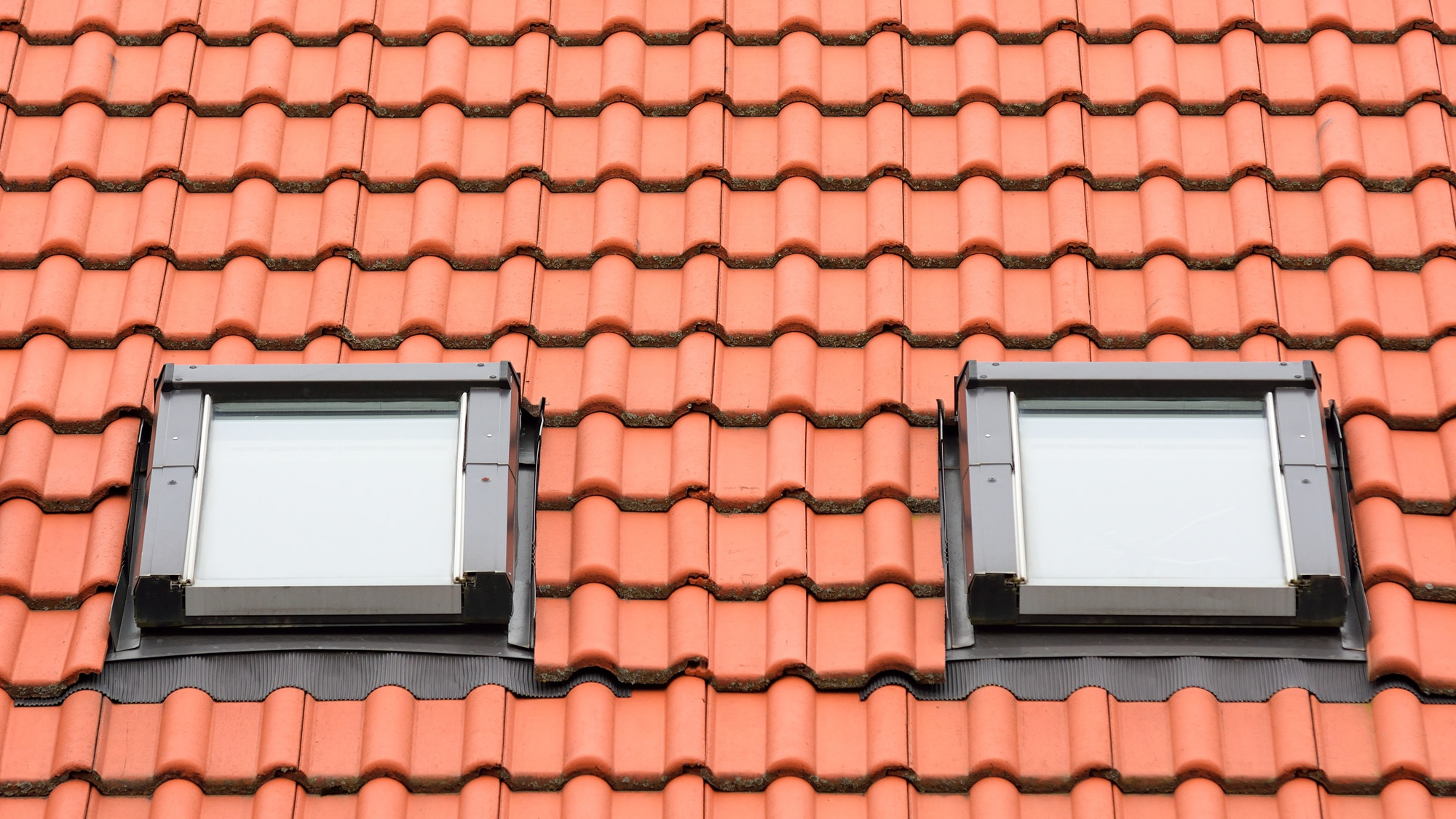 Exterior view of two new side by side skylights on tile roof